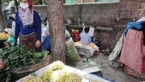 Annesiyle pazarda sebze satarken canlı derse katılan çocuk..